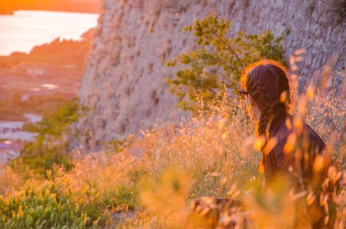 Sunset in Croatia - from Sibenik castle with woman in grass