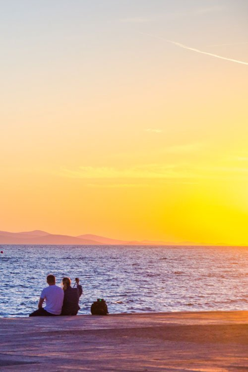 Sunset in Croatia - Zadar harbour front with couple