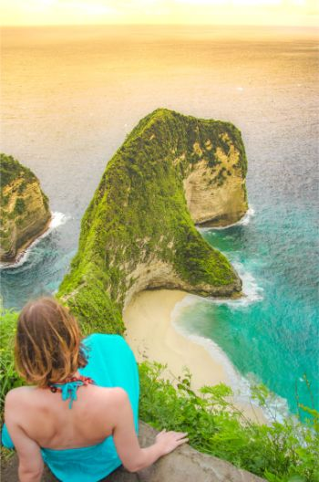 Woman sitting overlooking Kelingking Beach , Nusa Penida