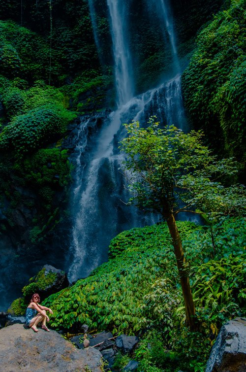 Niagara Sekumpul Waterfall  with young woman sitting on a rock and surrounded by lush tropical vegetation