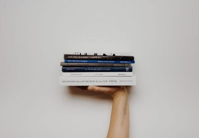 Person holding up stack of books