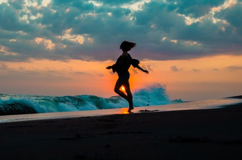 Jumping in front of the setting sun and crashing waves