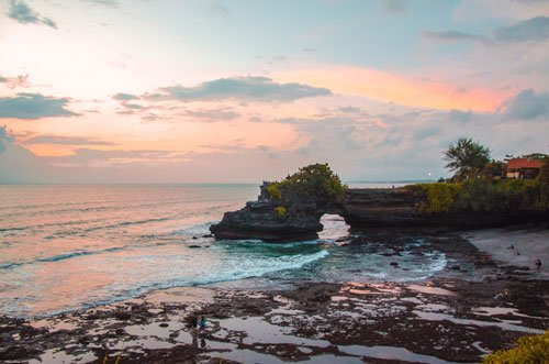 Pura Batu Bolong and low tide at Tanah Lot beach with orange clouds at sunset hour