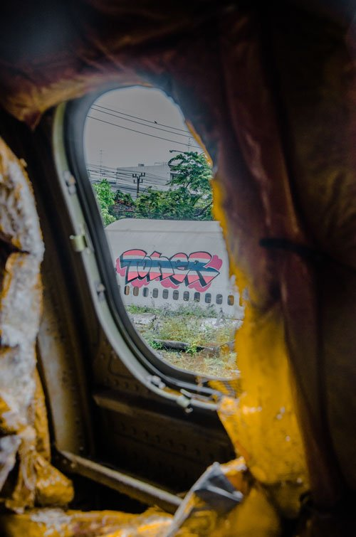 looking out of the passenger window to the homeless shelter on the airplane graveyard Bangkok