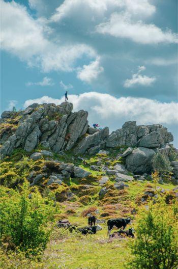 Hiker standing atop Greator Rocks in Dartmoor National Park