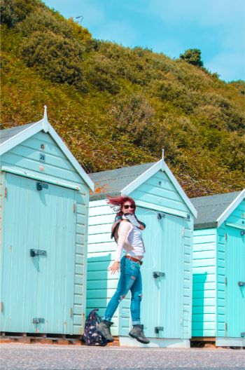 Bournemouth beach huts in baby blue with jumping woman