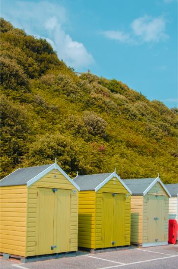 Bournemouth beach huts in lemon yellow underneath green hills