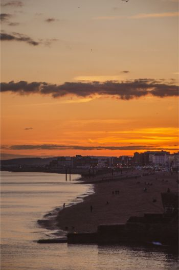 view from the pier over Brighton at sunset set to a orange and golden sky