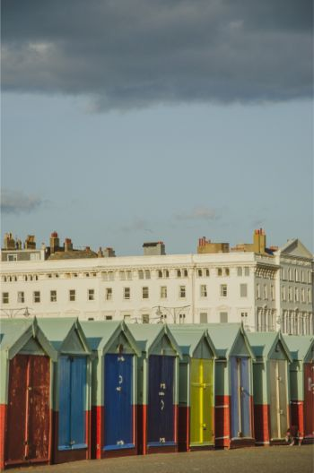 Brighton beach huts in raibow colours with awhite townhouse in the background