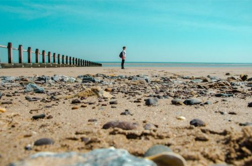 woman at low tide on beach of Dawlish Warren, Devon, England