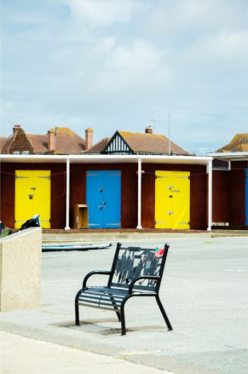 Westgate-on-Sea beach huts: red wooden blocks with yellow and blue doors