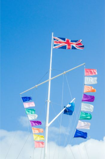 colourful flags swaying in the wind unerneath the Union Jack