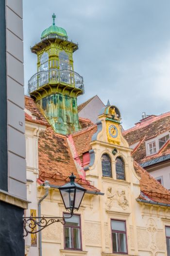 close of of architecture in Graz, Austria, with a golden clock on a beige coloured baroque building with green viewing tower
