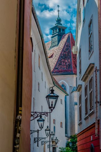 narrow street in Graz leading up to a church with an iron lamp in the foreground