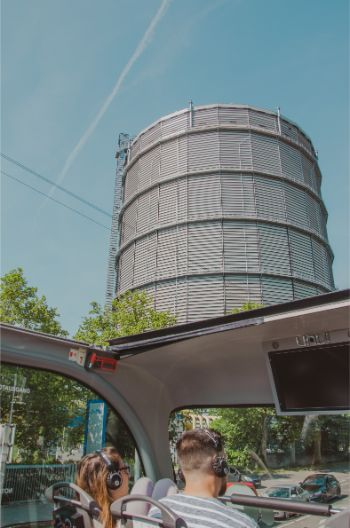 massive grey gas holder in Stuttgart as seen from an open deck at a tourist bus