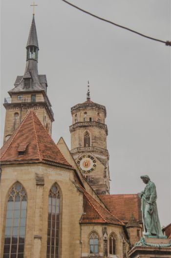 old church with clock tower and statue in the front in the centre of Stuttgart, Germany