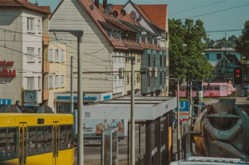 regular street tram station with a tram painted in bright pink and with a pig head in the distance