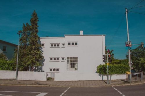 pristine white house designed in clear geometrical shapes with tiny square windows contrasting with the dark blue sky on a sunny day in Stuttgart