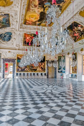 Castle Eggenberg and its chess pattern floor in the dancing hall with glistening chandeliers hanging from the Baroque ceiling, Graz, Austria