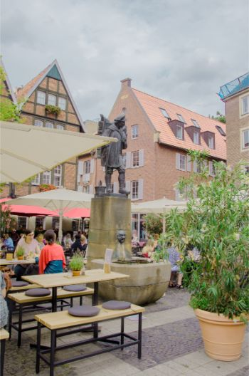 Kiepenkerl Square in Münster witht the iconic statue and restaurant patrons during lunch time