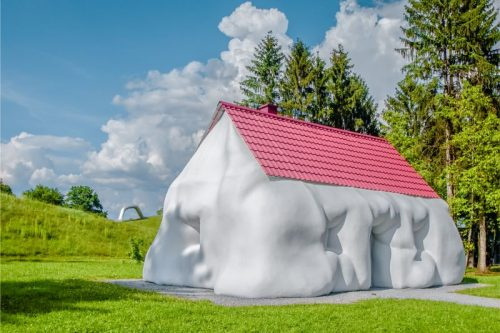oddly shaped sculpture of a house in stark white and with a red roof underneath a blue sky in the Graz sculpture park