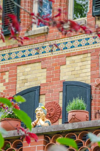 detail on house with red and yellow brickwork with cheeky woman scupture on balcony