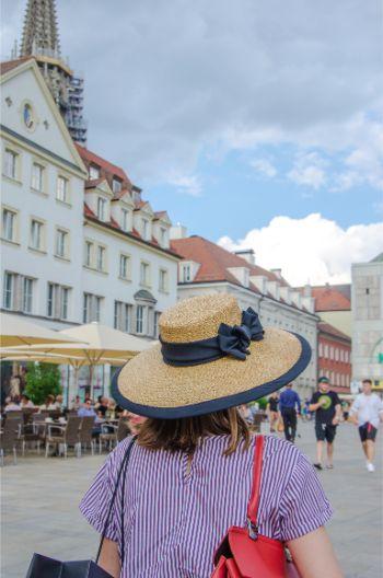 women in fancy hat walking through Regensburg, Germany
