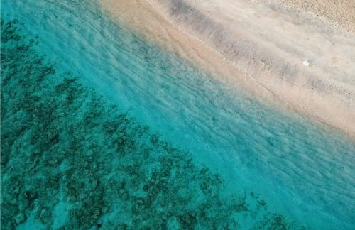 drone shot of beach and crystal clear blue water at Gili T, Indonesia