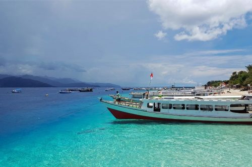 boats along the crystal clear blues of Gili T near Bali