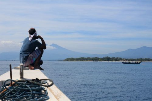 man sitting on a small boat facing the GIli islands in the distance