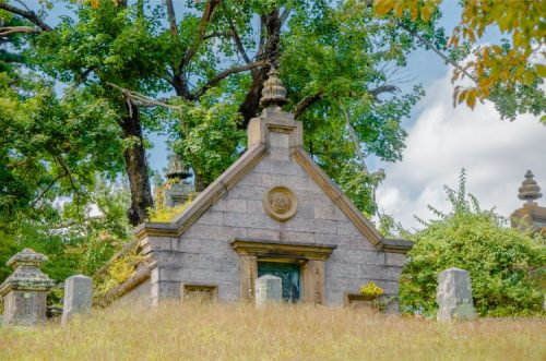 mausoleum hidden behind dry grass hill with graves at Sleepy Hollow CemeterySleepy Hollow cemetery NY