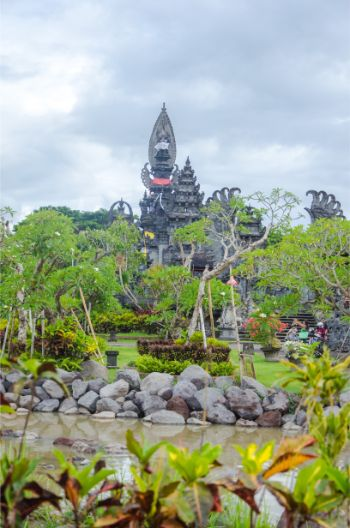 towering black stone buildings over the garden at Pura Jagat Nata
