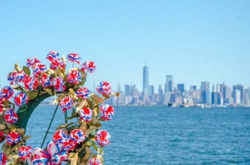 flowe wreaths in memory of 9/11 victims with view to Manhattan