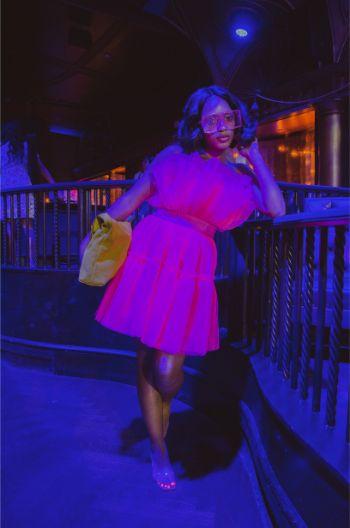 attendee of NYFW in pink dress under blue light