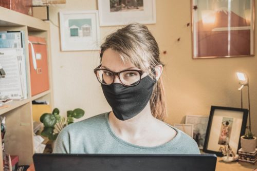 wearing a black cloth mask while working