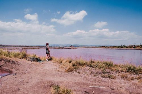 woman gazing out over pink lake in Bulgaria