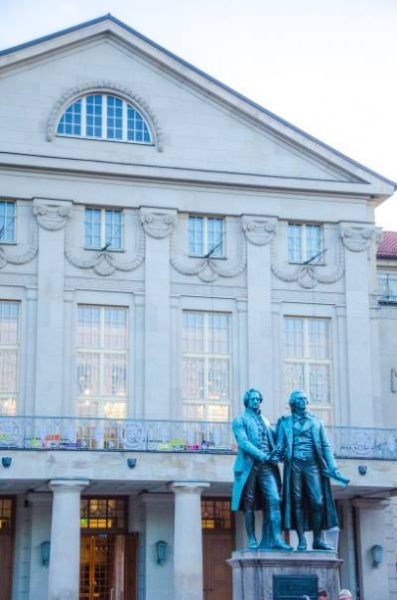 Schiller and Goethe statue in front of white theatre building
