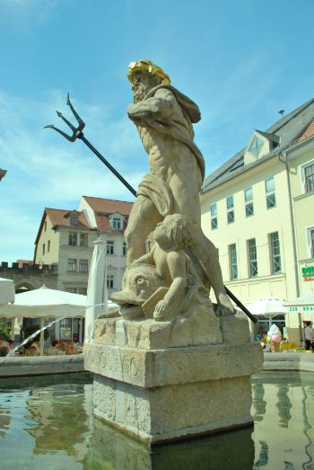 Triton statue on top of fountain on a sunny square