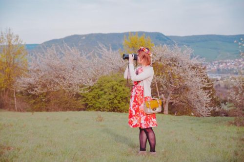 woman in red dress shooting photos among cherry trees in Jena